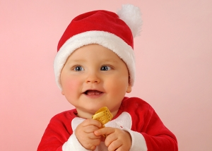 Baby als Weihnachtsmann mit Geschenk