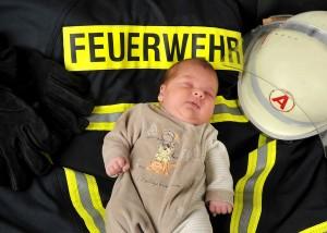 Baby mit Feuerwehr-Outfit