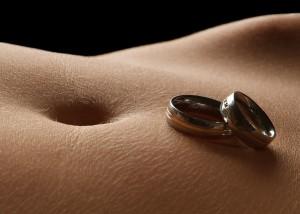 Nahaufnahme Eheringe auf Bauch liegend