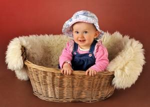Kind im Korb mit Muetze