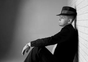 Portrait – Mann sitzend vor Mauer in schwarz-weiß